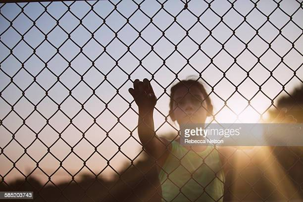 girl looking through chain link fence - chainlink fence stock pictures, royalty-free photos & images