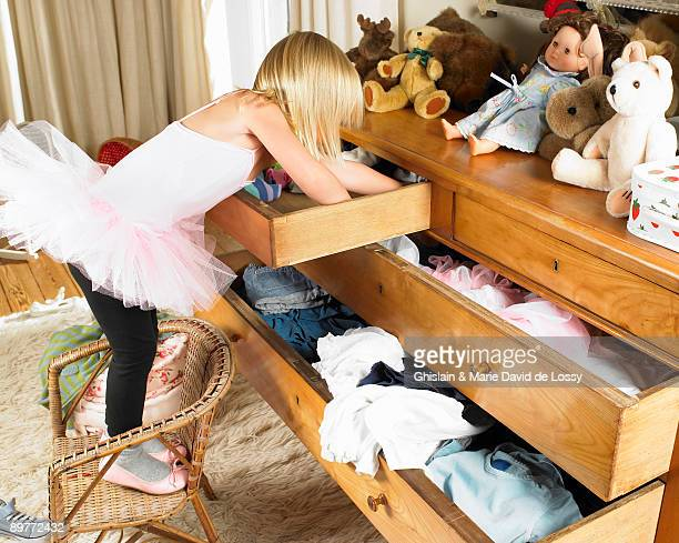 girl looking through drawers - girl chest stock photos and pictures