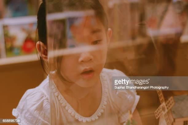 Girl looking through glass window display