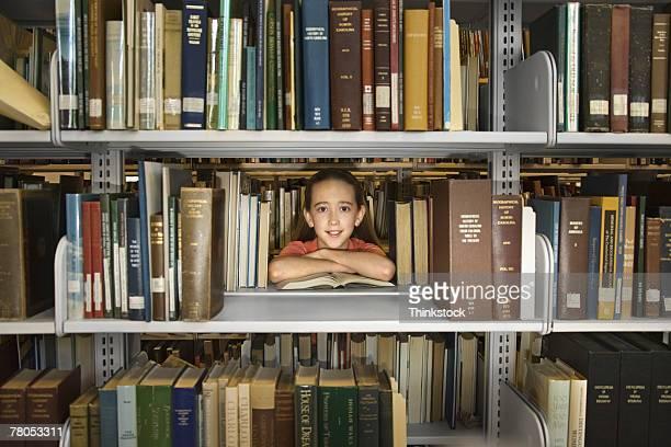 Girl looking through library shelf