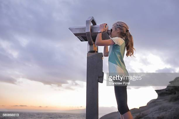 Girl looking through telescope, ocean and clouds