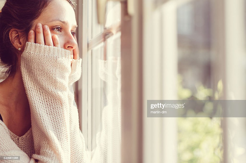Girl looking through the window : Stock Photo