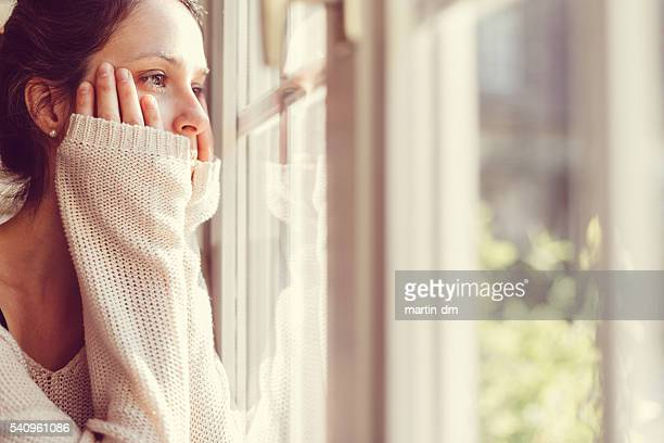girl looking through the window - ongerust stockfoto's en -beelden
