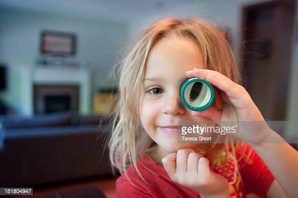 Girl looking through toy telescope