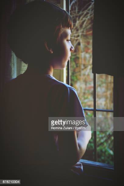 Girl Looking Through Window At Home