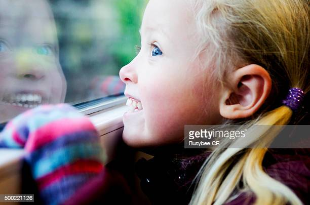 Girl looking through window of a train