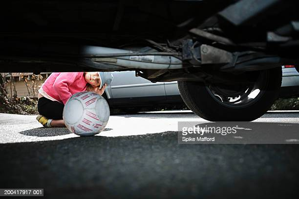 Girl (6-8) looking under car at ball, view from under car