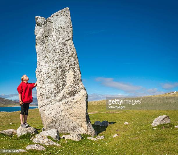 girl looking up at ancient stone monolith outer hebrides scotland - oude ruïne stockfoto's en -beelden
