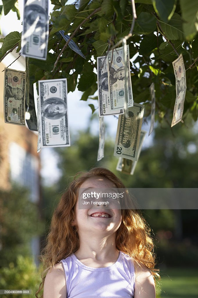 Girl (6-8) looking up at banknotes hanging from tree : Stock Photo