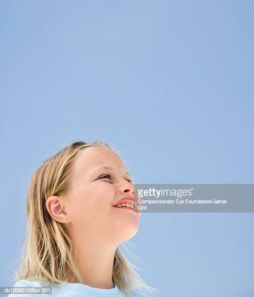 Girl (8-9) looking up at clear sky
