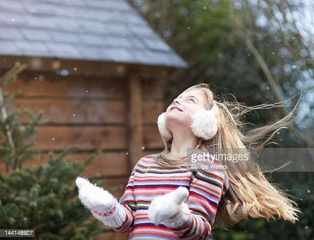 Girl looking up at falling snow.