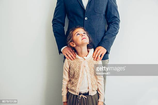 Girl looking up at her father standing behind her
