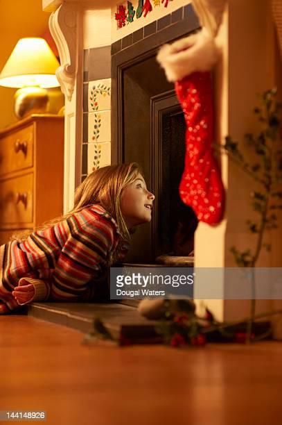 girl looking up chimney at christmas. - ligga på mage bildbanksfoton och bilder