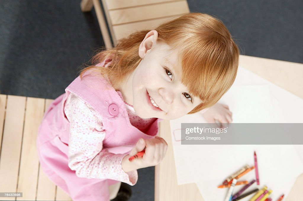 Girl looking up from coloring : Stock Photo