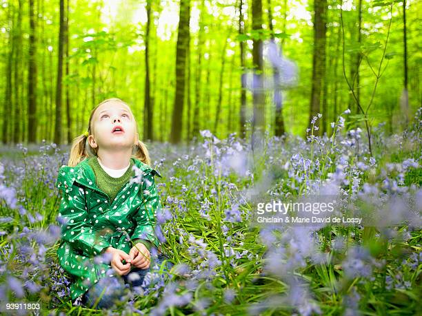 Girl looking up, in the woods