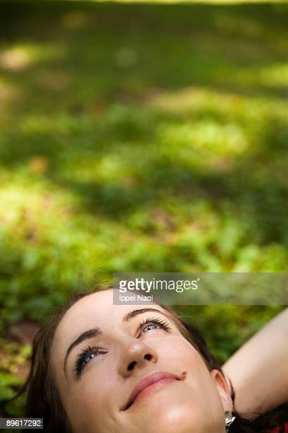 girl looking up smiling on the grass - ippei naoi stock photos and pictures