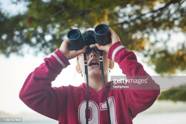 girl looking up through binoculars - heshphoto stock pictures, royalty-free photos & images