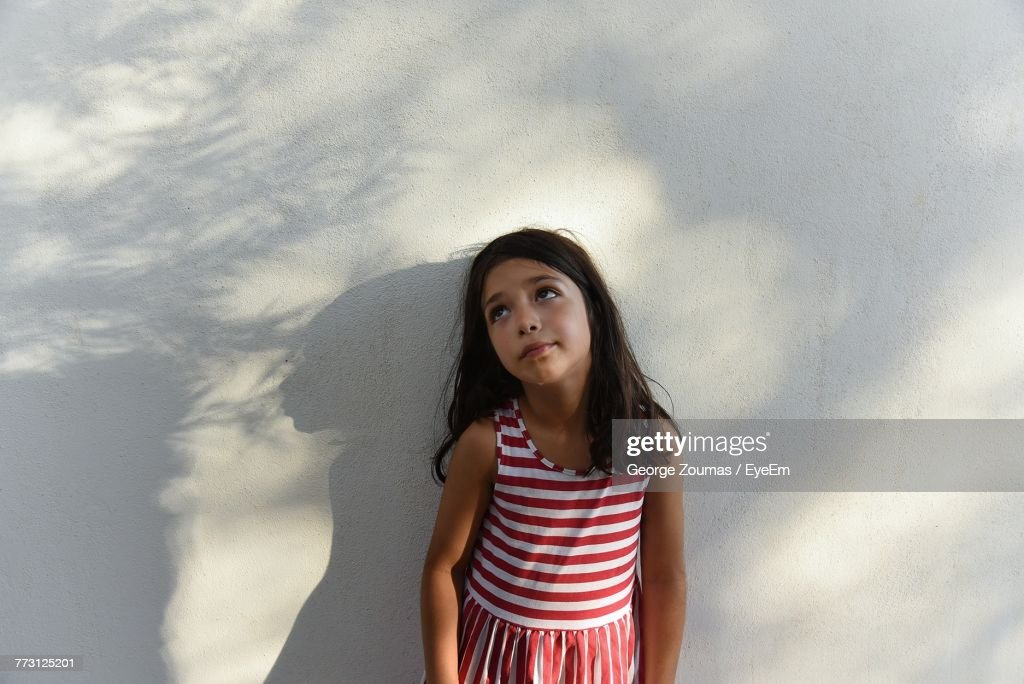 Girl Looking Up While Standing Against White Wall : Photo