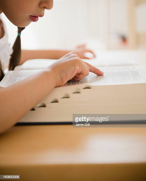 Girl looking up word in dictionary