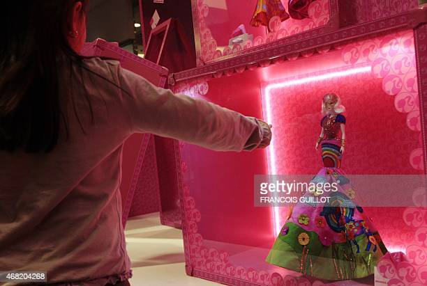 A girl looks at a Barbie doll dressed up in a creation of Indian designer Manish Arora on April 6 2009 in Paris during a visit of the Barbie Fashion...