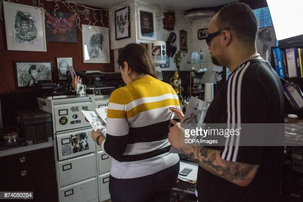A girl looks at a image that it going to tattooed on her back A tattoo artist is preparing the tattoo inks inks which designed t put onto the back of...
