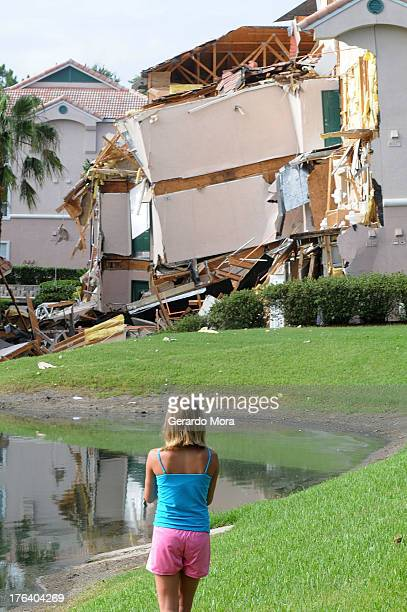 A girl looks at a partially collapsed building over a sinkhole at Summer Bay Resort near Disney World on August 12 2013 in Clermont Florida The 40 to...
