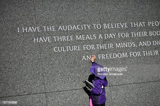 A girl looks at a quote at the Martin Luther King Jr memorial on the National Mall January 15 2012 in Washington DC Martin Luther King III and others...
