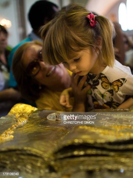 A girl looks at a relic after a mass officiated by Cardinal Stanislaw Rylko to celebrate the arrival in Brazil of the relics of blessed John Paul II...
