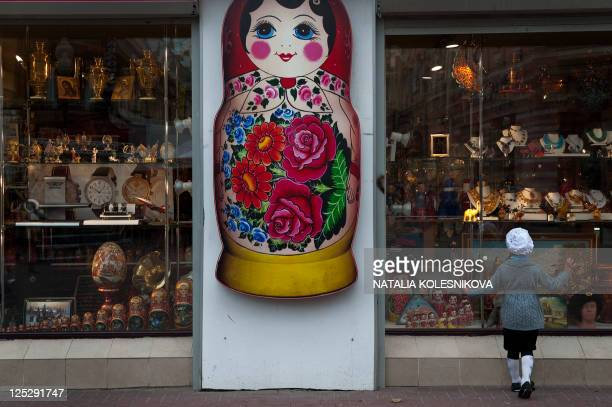 A girl looks at a souvenir shop window at the pedestrian Arbat street in downtown Moscow on September 16 2011 in Moscow AFP PHOTO / NATALIA...