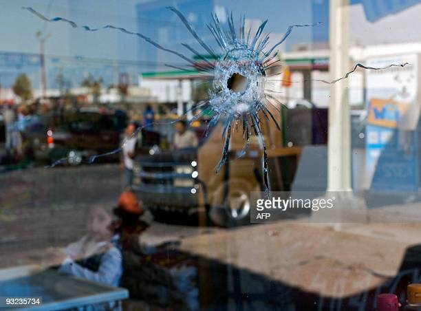 A girl looks at a window with a hole made by a shot near the place where two policemen were killed in Ciudad Juarez Mexico on November 19 2009 Four...