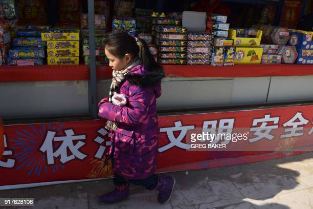 A girl looks at fireworks at a stall on the outskirts of Beijing in the buildup to Lunar New Year celebrations on February 13 2018 Beijing has banned...