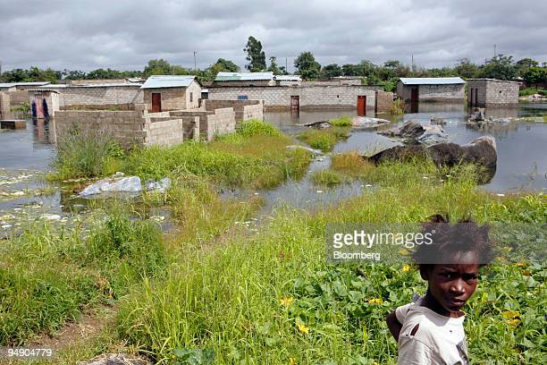 A girl looks at flood water in the John Laing area of Lusaka Zambia on Tuesday Jan 29 2008 About 68 percent of Zambians currently live below the...