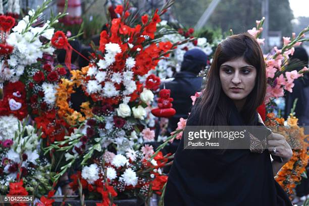 A girl looks at fresh roses flowers bouquets and garlands for her loved ones from a big flower wholesale market on the eve of World Valentine's Day