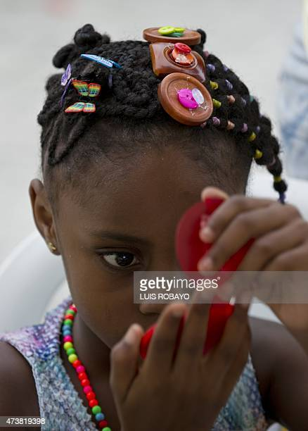 A girl looks at her AfroColombian hairstyle in the mirror during the 11th Afrohairdressers contest Tejiendo Esperanzas on May 17 in Cali Valle del...