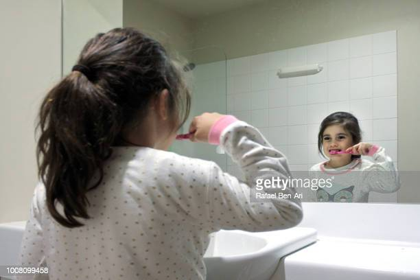 Girl Looks at Herself in the Mirror while Brushing Teeth
