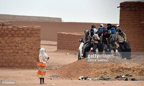A girl looks at migrants sitting on the open cargo of a pickup trucks= holding wooden sticks tied to the vehicle to avoid falling from it as they...