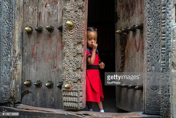 A girl looks at passers on a street of the Stone Town in Zanzibar City Zanzibar Tanzania on 11 October 2016
