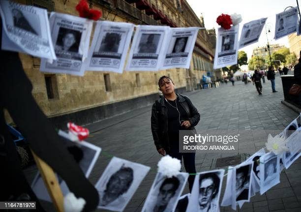 A girl looks at pictures of missing persons hanging from a rope in front of the National Palace during the commemoration of the International Day of...