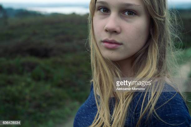 A girl looks at the camera on a background of a green meadow