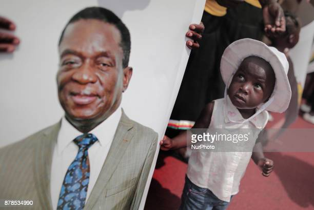 A girl looks at the image of the new president Emmerson Mnangagwa during the ceremony officially swornin in Harare on November 24 2017 Emmerson...