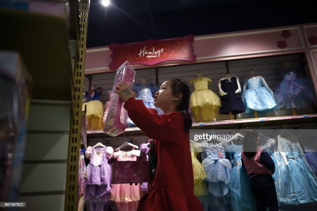 A girl looks at toys on the opening day of a new Hamleys store, the iconic British toy retailer now Chinese-owned, in Beijing on December 23, 2017. The well-loved British toy retailer, which was sold to a Chinese company in 2015, first opened in 1760 and has been expanding internationally, opening stores in locations ranging from Moscow to Dubai. /