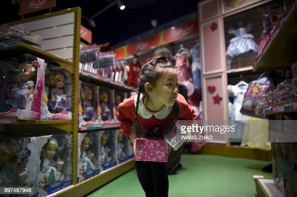A girl looks at toys on the opening day of a new Hamleys store the iconic British toy retailer now Chineseowned in Beijing on December 23 2017 The...