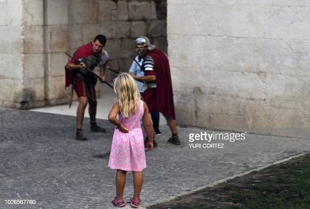 A girl looks at two actors disguised as Roman soldiers who perform with tourists in the socalled Golden Gate of Diocletian's Palace located inside...