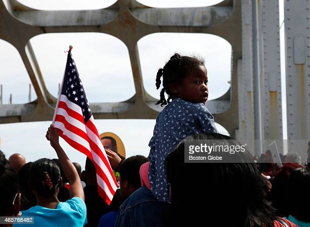 A girl looks back as she is carried across the Edmund Pettus Bridge as she and thousands of others retrace the steps of those who marched with Dr...