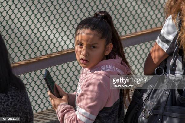 A girl looks back at Los Angeles Fire Department Task Force 12 firefighters who salute as a procession carries the body of Cory Iverson a fire...