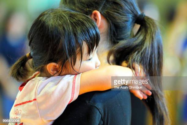 A girl looks exhausted on her mother's chest as sweltering heat hit after flooding at an evacuation center on July 11 2018 in Hiroshima Japan The...