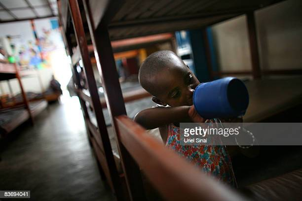 A girl looks for more food in her empty cap as Congolese child refugees some orphaned or separated from their family after conflict in the region...