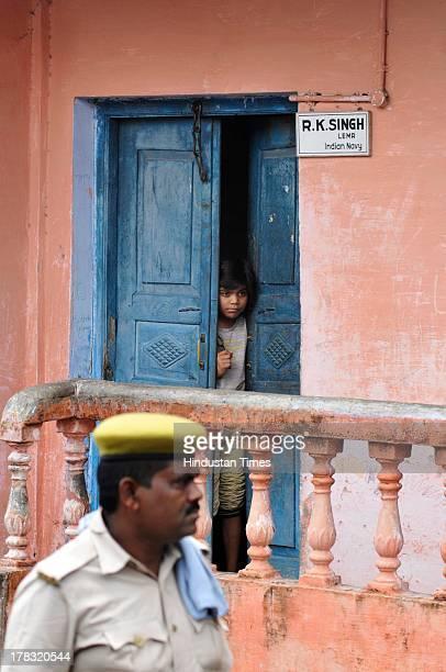 Girl looks from inside the doors as policeman patrols the streets in wake of Vishwa Hindu Parishad's 84 Kosi yatra, which was banned by Uttar Pradesh...