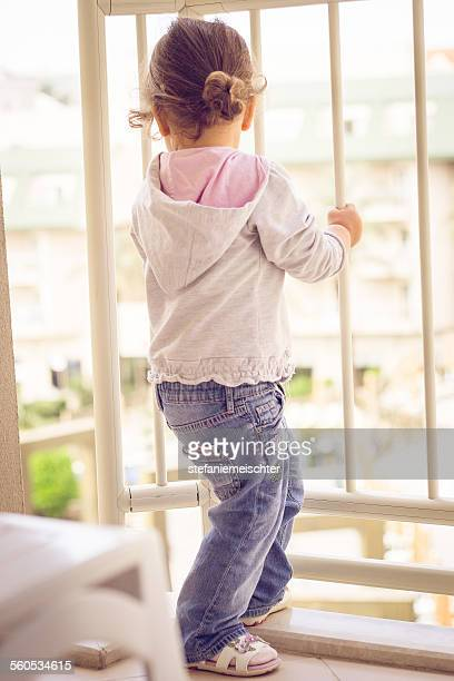 girl looks into the distance - child behind bars stock pictures, royalty-free photos & images