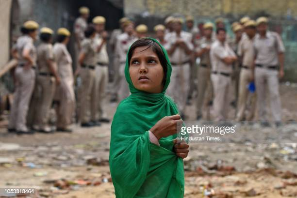 A girl looks on as heavy deployment of police force is seen in the backdrop after an eightyearold student of a Madrasa died after he sustained a head...